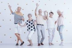 Personnes supérieures heureuses dansant sur le fond blanc avec de l'or d Photographie stock