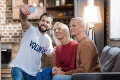 Personnes supérieures heureuses prenant des photos avec leur assistant social Image libre de droits