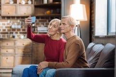 Personnes supérieures progressives tenant un téléphone intelligent tout en prenant des photos Photos libres de droits