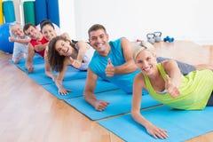 Personnes sur des tapis d'exercice faisant des gestes des pouces au gymnase Photos libres de droits