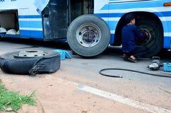 Personnes thaïlandaises de mécanicien réparant et pneu de roue de changement de difficulté d'autobus images stock