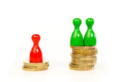 Persons with differences in income. Shown in stacks of coins and pawns Stock Photography