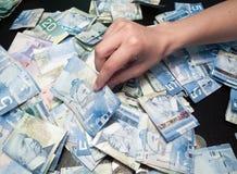 Persons händer som väljer räkningen för kanadensisk dollar fem Royaltyfri Fotografi