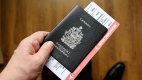 Persons hand holding a passport of Canada Stock Image