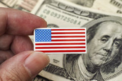 Persons hand holds American Flag badge against heap of dollar bi Stock Photography