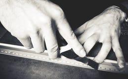 Persons hand som arbetar med en linjal arkivbild