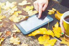 Persons hand using a tablet on a wooden table Royalty Free Stock Image