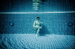 Persons lies under water in a swimming pool Stock Photos