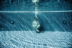 Persons lies under water in a swimming pool Royalty Free Stock Image