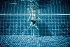 Persons standing under water in a swimming pool Royalty Free Stock Photography