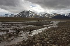Persons traveling across arctic tundra Stock Images