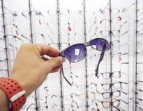 Persons välja för hand exponeringsglassolglasögon på optiklagret arkivfoton