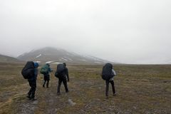 Persons Walking Tundra in Svalbard Royalty Free Stock Photography