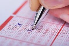 Persoon die aantal op loterijkaartje merken Royalty-vrije Stock Fotografie