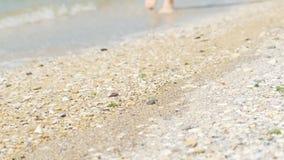 Persoon die blootvoets langs het zonnige strand lopen stock video
