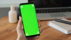 Persoon die celtelefoon met groene het schermvertoning ter beschikking met behulp van stock videobeelden