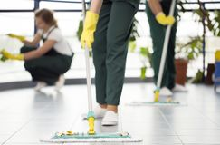 Persoon die de vloer schoonmaken stock fotografie