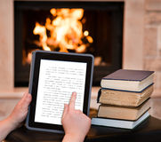 Persoon die digitale tabletpc met behulp van dichtbij de open haard Royalty-vrije Stock Foto's