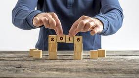Persoon die een brug van houten kubussen met het jaar 2016 teken bouwen Royalty-vrije Stock Foto's