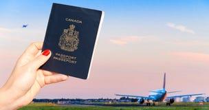 Persoon die een Canadees paspoort met één en een andere vliegtuig houden die taxi?en opstijgen stock fotografie