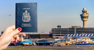 Persoon die een Canadees paspoort met luchthaven eindachtergrond houden stock fotografie