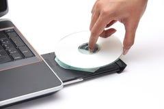 Persoon die een compact disc plaatst in de CD-romaandrijving royalty-vrije stock afbeelding