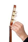 Persoon die een gitaar van zijn asblok stemmen Stock Fotografie