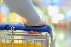 Persoon die een karretje duwen door een supermarkt Stock Afbeelding