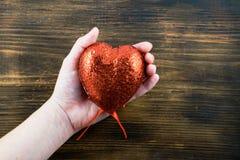 Persoon die een met de hand gemaakt rood hart in haar handen houden Liefde 14 van Februari De dag van de valentijnskaart `s Stock Afbeelding