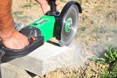 Persoon die een stuk van beton snijden Royalty-vrije Stock Foto's