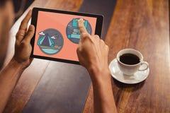 Persoon die een tablet met reispictogrammen houden op het scherm Stock Foto