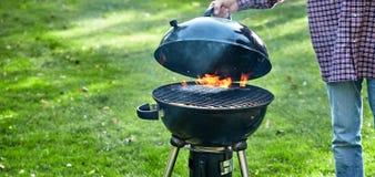 Persoon die het deksel op een brand in draagbare BBQ opheffen stock fotografie
