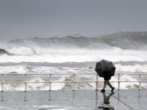 Persoon die met paraplu in een regenachtige en winderige dag beschermen Royalty-vrije Stock Afbeelding