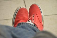 Persoon die rode schoenen en jeans gekruiste benen dragen Stock Afbeeldingen