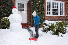 Persoon die sneeuw schept Stock Afbeelding