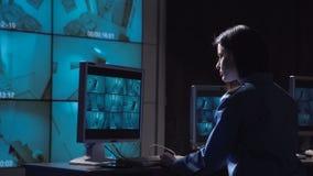 Persoon die toezicht met gesloten circuit controleren stock footage