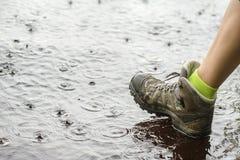 Persoon die in wandelingslaarzen op water in de regen lopen Stock Foto's