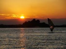 Persoon die windsurf in de vakantie met de zonsondergang op de achtergrond opleiden stock foto's