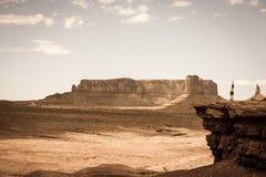 Persoon die zich op steenrichel bevinden voor een woestijnlandschap Stock Foto's