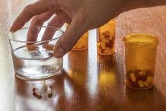 Persoon genomen zijn dagelijks medicijn met een waterglas royalty-vrije stock foto's