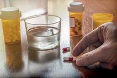 Persoon genomen zijn dagelijks medicijn met een waterglas royalty-vrije stock afbeeldingen