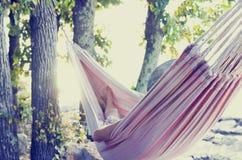 Persoon het ontspannen in een hangmat, met retro filtereffect Stock Afbeeldingen