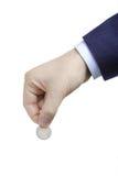 Persoon met een muntstuk in zijn hand stock foto's