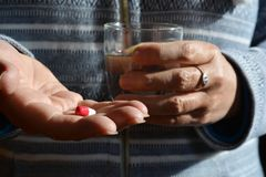 Persoon met rood & wit capsule en glas zoet water stock foto
