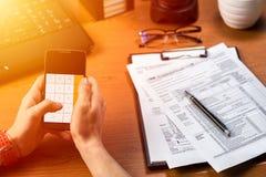 Persoon met smartphoneberekening zijn 1040 belastingsvorm Stock Foto's