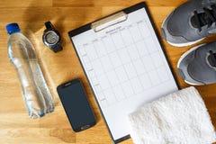Persoonlijk trainingplan met telefoon en ander materiaal stock fotografie