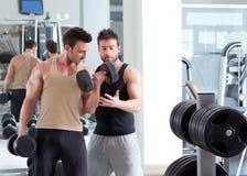 Persoonlijke de trainermens van de gymnastiek met gewichtheffen stock afbeelding