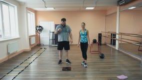 Persoonlijke opleiding van atletische instructeur voor de vette mens in gymnastiek of geschiktheidscentrum Fatboy en zwetend na o stock video