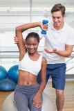 Persoonlijke trainer die de domoor van de cliëntlift op oefeningsbal helpen Stock Foto's