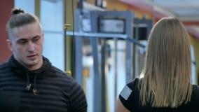 Persoonlijke trainer die op jonge vrouw letten die barbells in de gymnastiek gebruiken stock footage